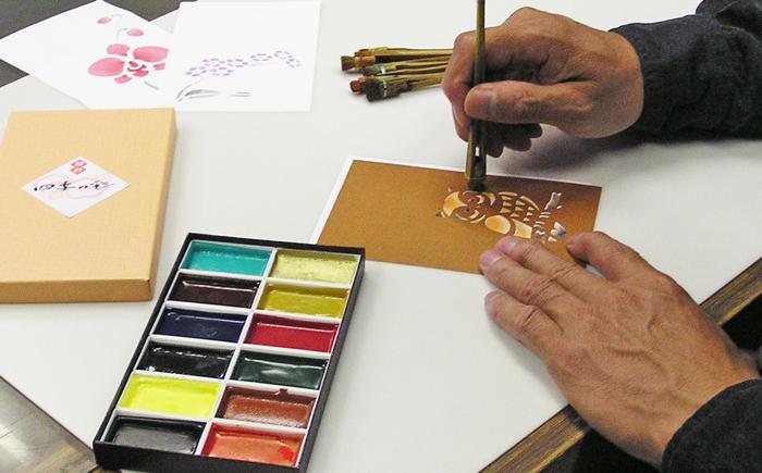 手作り年賀状を型紙を使って作成(顔彩絵の具と刷毛で彩色)している場面